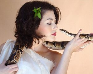 Woman (dressed as the Biblical Eve) looking into a snake's eyes
